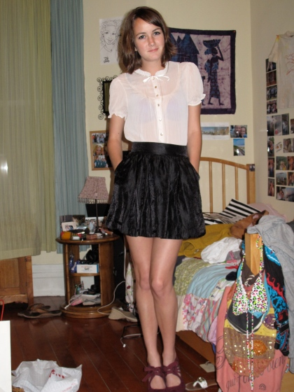 Becca pairs her shoes with a cream colored blouse and a black skirt both from H&M